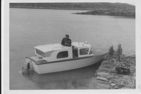 Torbjørn Helgesen i selvlaget plastbåt. Åge og Anny står ved siden av båten.