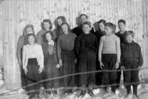 Storskolen 1946-47 | (4.-7.klasse ).  Fra venstre foran: Elisabeth Pedersen, Elsa Lind, Gerda Helgesen, Arnt Kristensen, Nils Hansen og Knut Helgesen.  Bak fra venstre: Paula Havn, Gunlaug Hansen, Dagny Slotvik, lærer Ola Lunde, Torleif Andersen og Helge Karlsen.  Erna Olsen og Norma Karlsen var ikke tilstede da bildet ble tatt.