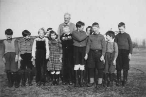 Småskolen 1952-53 | Fra venstre: Jan Petter Henriksen, John Klausen, Liv Havn, Nils Andersen, Olaug Nilsen, Paul Havn, Bjarne Murbræch, Ronald (el Bjørn) Lind, Atle Henriksen, Roald Henriksen og Knut Hagen.  Bak står lærer Andreas Moe som var lærer skoleåret 1952-53.