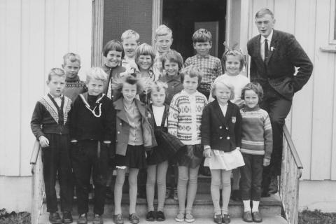 Skoleåret 1964-65 | Arnt O. Åsvang var lærer for småskolen (1.-3.klasse).  1. rekke fra venstre: Ernst Våg, Kjell Klausen, Birgith Waag, Mary-Ann Lyng, Åshild Klausen, Alfhild Larsen og Gerd Johansen . 2. rekke fra venstre: Dagfinn Sørensen, Elsa Hagen, Frøydis Mikalsen, Ninni Skulstad og Beate Olsen.  Bakerste rekke fra venstre: Helge Våg, Sigbjørn Klausen og Willy Larsen.